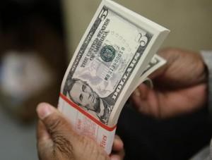 Una persona revisando un paquete con billetes de 5 dólares en la Casa de la Moneda de Estados Unidos en Washington